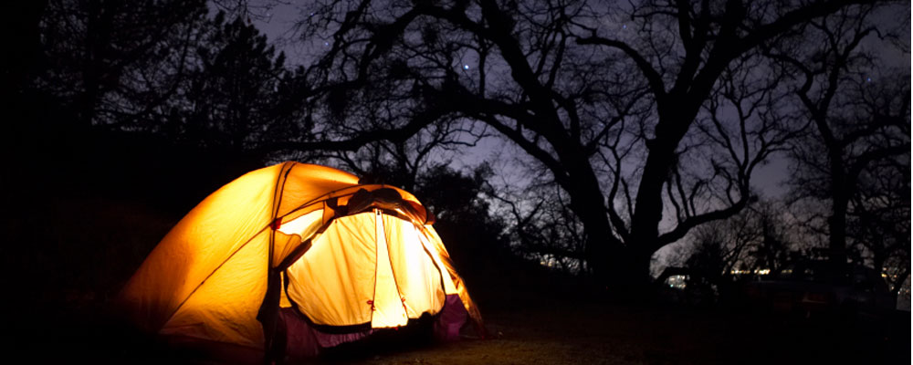 a tent at night lit up under the stars